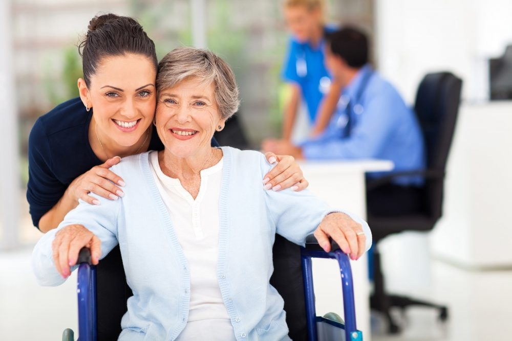 Senior woman in wheelchair with senior caregiver